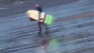 White surfboard guy walking across beach oh no