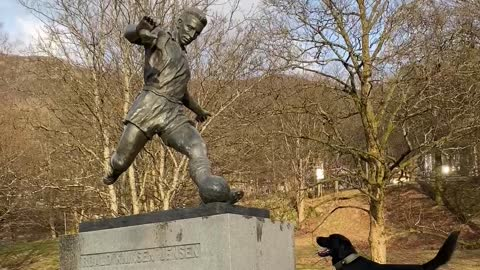 Dog sees statue of man kicking soccer ball, waits to chase after it