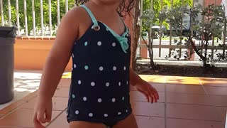 Little girl dances by the pool