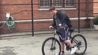 Shorts backpack kid does wheelie on bike and falls on back