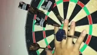 Slowmotion dart barely misses finger on board at night - Video