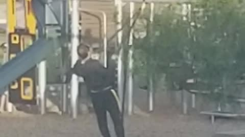 Man in black exercising in playground with ropes