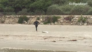 Surfer walking on beach with surfboard tied to leg following him