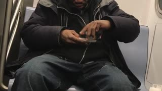 Man rolls cigarette while sitting on subway - Video
