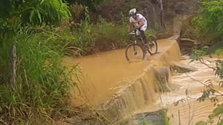 Guy on bike takes epic fall into river - Video