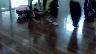 Little girls holding onto each others neon green shirts one girl in red falls and hits floor