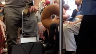 Guy pushing speaker playing trumpet subway