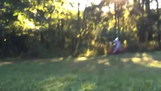 Person falls off of red motorcycle dirt bike grass