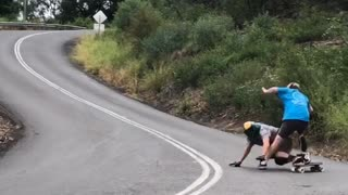 Downhill Skateboarder Takes Out Cameraman