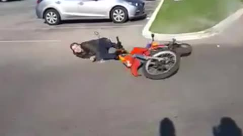 Man falls off a red dirt motorcycle