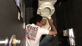 Guy white shirt on ground throwing up in sink - Video