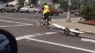 Guy on bike with his surf board behind him - Video