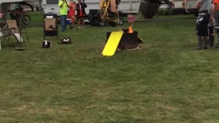 Guy in orange shirt does ramp jump over small fire on mini motorcycle