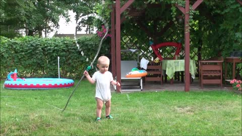 Baby watering the grass