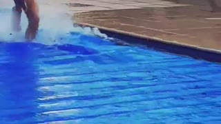 Guy in red shorts running on top of blue sheet in pool - Video