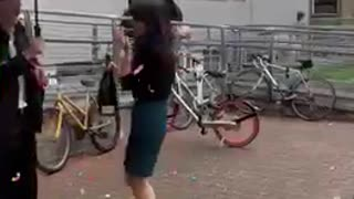 Girl holding champagne bottle gets startled by cork that hits umbrella