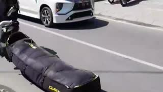 Guy dragging black bag on floor ground street while riding motorcycle with helmet