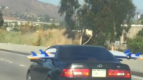 Person driving on freeway with surfboard through back seat windows