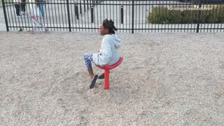Girl on red spinning chair at park