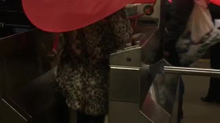 Two people subway turnstile red umbrella hats