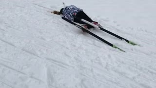 Girl trying to run in skis falls forward into snow