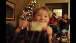Boy dances with his christmas present and rips it in half - Video