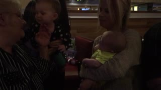 Adorable baby kisses her baby cousin