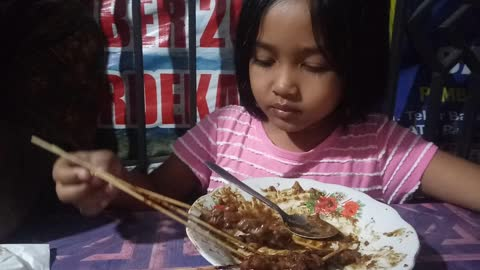 Little Girl Like to Eating satay with peanut sauce