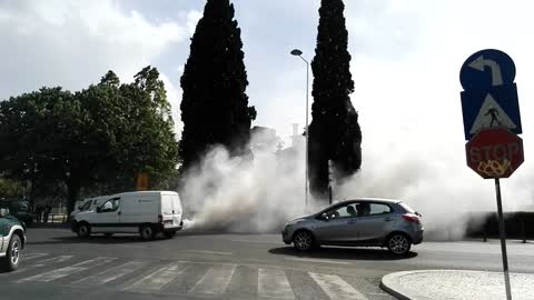 Massive smoke cloud behind car that seems almost ready to explode