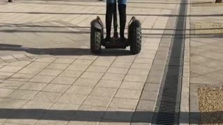 White coat girl rides segway down sidewalk and faceplants - Video