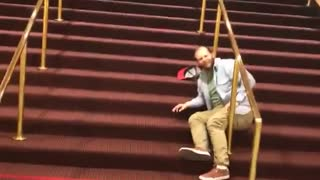 Blue shirt tries slide down gold railing on red stairs and falls