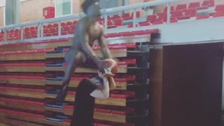 Shirtless guy jumps over friend to shoot basket in hoop
