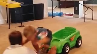Baby riding tiny plastic car runs into guy and they bump heads - Video