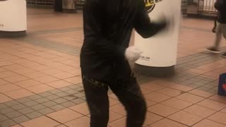 Guy with flashing grills dances in a subway