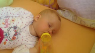 Sleepy baby falls asleep while drinking bottle - Video