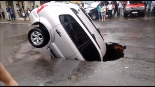 Car Sinks Into Major Pothole
