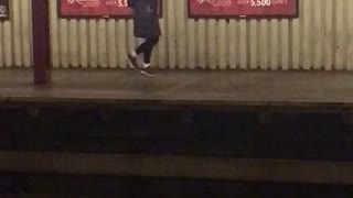 Hoodie woman does odd dance while waiting for subway