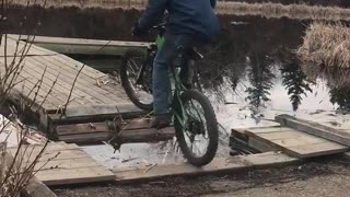 Guy in green bike rides into lake
