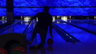 Guy at bowling alley falls when he throws ball  - Video