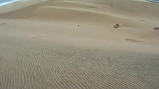Go pro blue board surfs sand dune falls down - Video