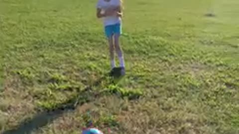 Girl gets hit in the stomach after sister kicks soccer ball and laughs
