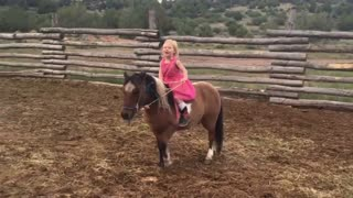 Little Girl Rides and Sings with Her Pony
