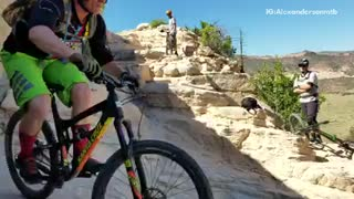 Guy green shorts mountain bike going down mountain rocks fail