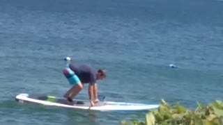 Man Struggles with Lakeside Paddleboard