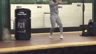 A woman in grey sweatsuit dances on subway station