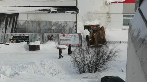 The tractor cleans the road from snow.