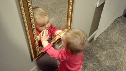 Curious baby fascinated by reflection