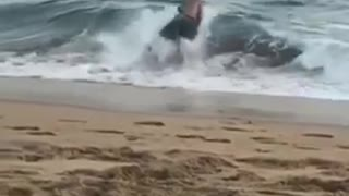 Guy running into wave gets flipped over and falls  - Video