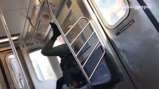Guy in black jacket dancing head stand blue subway seat - Video