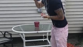Guy with pink shorts opens beer with his head  - Video